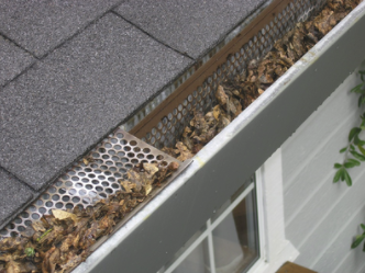 A gutter that desperately needs gutter cleaners to do a leaf relief service.